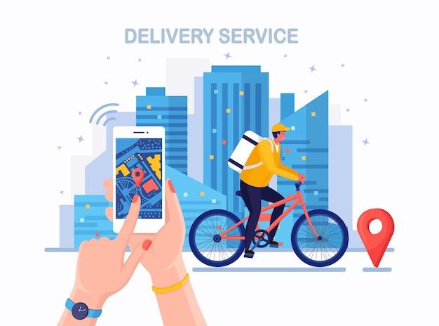 Servizio di consegna veloce gratuito in bicicletta. il corriere consegna l'ordine del cibo. tenere in mano il telefono con l'app mobile. monitoraggio del pacco online. l'uomo viaggia con un pacco in giro per la città