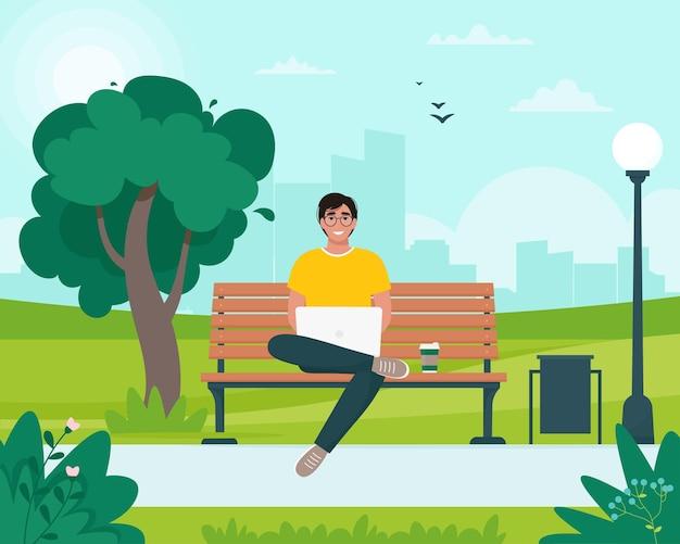 Uomo libero professionista seduto su una panchina con un computer portatile nel parco