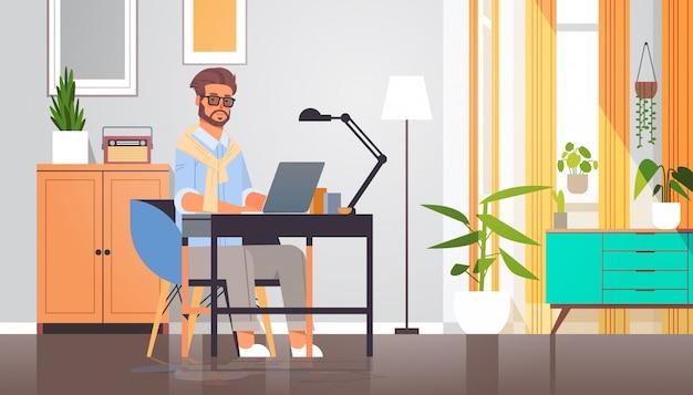 Libero professionista con laptop uomo seduto sul posto di lavoro autoisolamento coronavirus quarantena pandemia