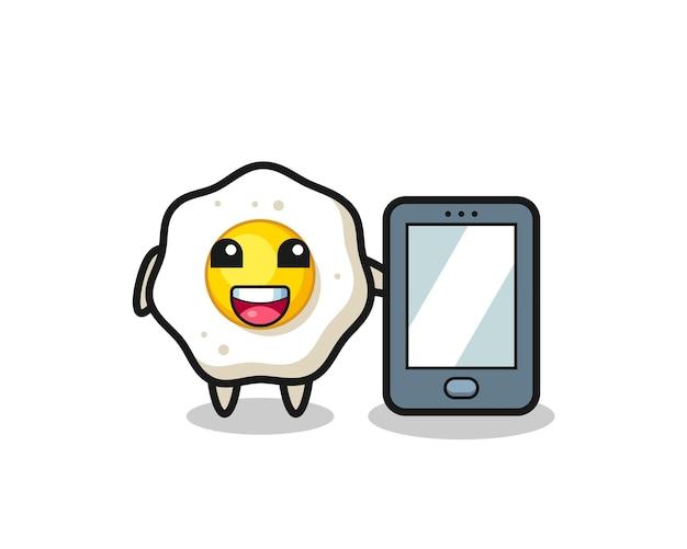 Fumetto dell'illustrazione dell'uovo fritto che tiene uno smartphone, design in stile carino per maglietta, adesivo, elemento logo