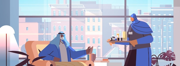 Infermiera araba amichevole o volontario che porta pillole ai servizi di assistenza domiciliare del paziente arabo dell'uomo anziano