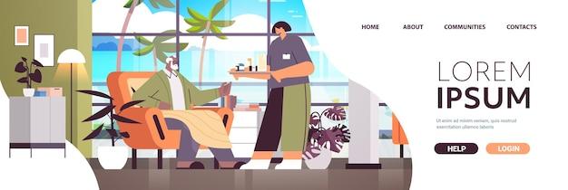 Infermiera o volontaria amichevole che porta pillole a un uomo anziano afroamericano servizi di assistenza domiciliare per pazienti concetto di supporto sanitario e sociale orizzontale spazio di copia a figura intera