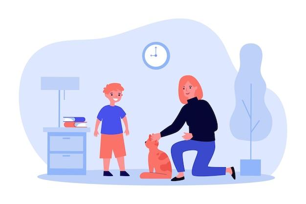 Mamma amichevole che accarezza il gatto mentre parla al piccolo figlio