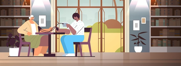 Infermiera amichevole o volontario che controlla la pressione sanguigna alla donna anziana servizi di assistenza domiciliare del paziente concetto di supporto sanitario e sociale casa di cura interno orizzontale a figura intera