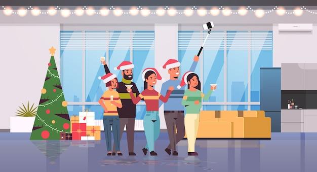 Amici che celebrano la festa di natale prendendo selfie foto sulla fotocamera dello smartphone uomini donne in cappelli di babbo natale divertirsi buon natale felice anno nuovo concetto di vacanze moderno soggiorno interno