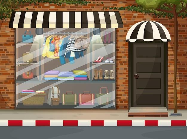 Parte anteriore della vetrina del negozio di abbigliamento con vestiti e accessori