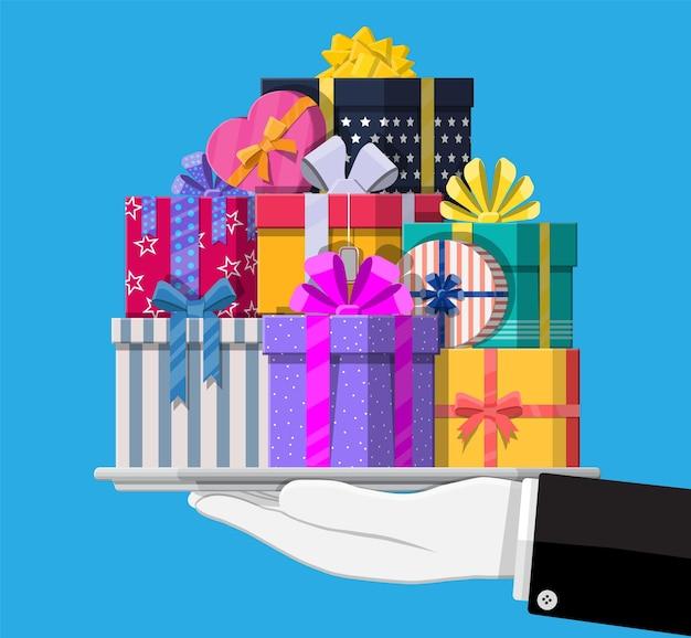 Scatole regalo in mano. incartato colorato. vendita, acquisto. presenti scatole di diverse dimensioni con fiocchi e nastri. collezione per compleanni e vacanze. illustrazione vettoriale in stile piatto