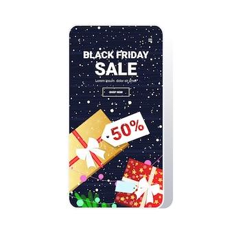 Scatole regalo con tag grande vendita venerdì nero offerta speciale promo marketing concetto di shopping natalizio schermo dello smartphone app mobile online