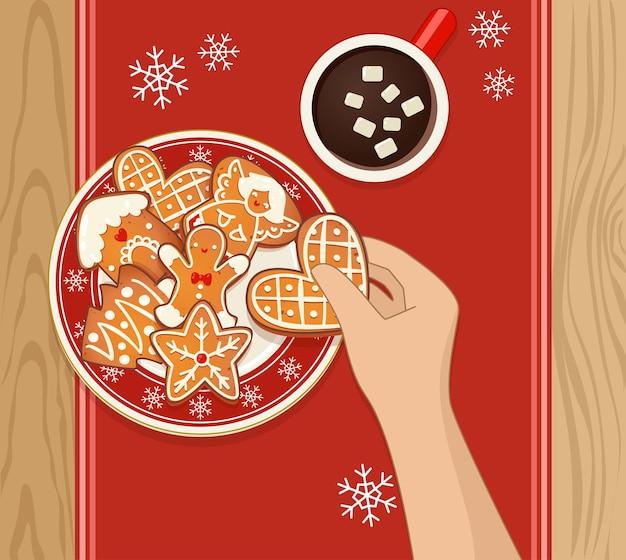 Biscotti di natale di panpepato sulla zolla rossa con fiocchi di neve e cioccolata calda. mano umana che tiene un biscotto. illustrazione vettoriale vista dall'alto per il nuovo anno e il design delle vacanze invernali.