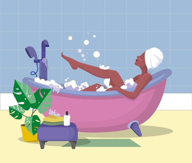 La ragazza in bagno. una ragazza con un asciugamano in testa fa un bagno di bolle. concetto.