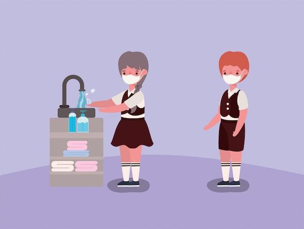 Bambini del ragazzo e della ragazza con le maschere mediche che si lavano le mani