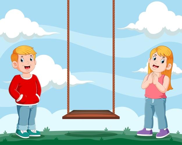 Ragazza e ragazzo in piedi l'altalena in legno per giocare insieme in giardino
