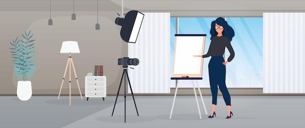 La ragazza sta facendo una presentazione davanti alla telecamera. l'insegnante conduce una lezione online. il concetto di blog, formazione online e conferenze. fotocamera su treppiede, softbox.