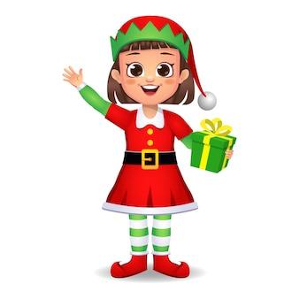 Ragazza ragazzino in vestito da elfo dicendo ciao con il regalo