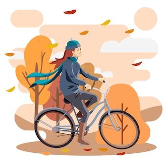 Ragazza che guida la bici in autunno