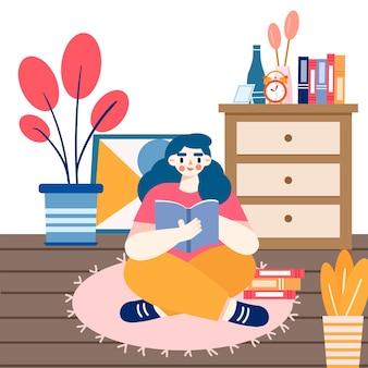 Una ragazza seduta sul pavimento di una stanza che legge e studia