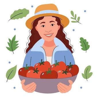 Ragazza in un cappello di paglia tiene un cesto di pomodori