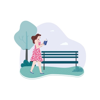 La ragazza cammina attraverso il parco e legge il libro