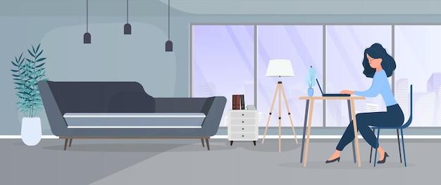 La ragazza lavora a un laptop in un ufficio elegante. uno studio, un computer, un divano, un armadio, una libreria con libri, quadri alle pareti. lavoro a casa. .