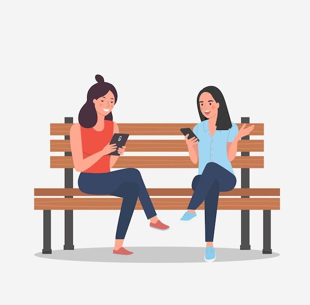 Le amiche sono sedute in panchina con gli smartphone. illustrazione di stile cartone animato piatto