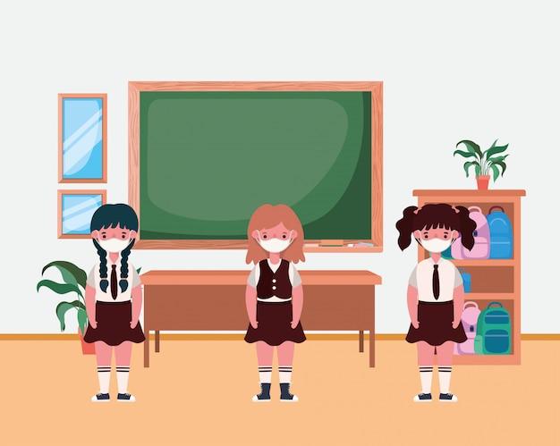 Bambini delle ragazze con le maschere in aula