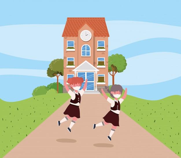 Bambini delle ragazze con le maschere che saltano davanti alla scuola