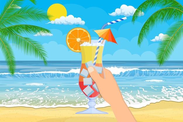 Bicchiere di bevanda fredda, cocktail alcolico in mano. paesaggio di palma sulla spiaggia.