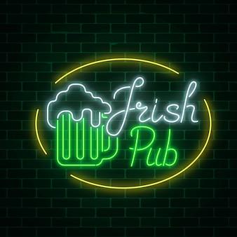 Insegna al neon irlandese d'ardore del pub nella struttura di ellisse sul fondo scuro del muro di mattoni. insegna pubblicitaria luminosa
