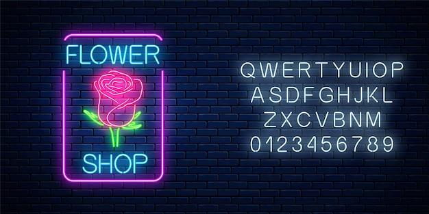 Insegna al neon incandescente del negozio di fiori in cornice rettangolare con alfabeto sul muro di mattoni scuri