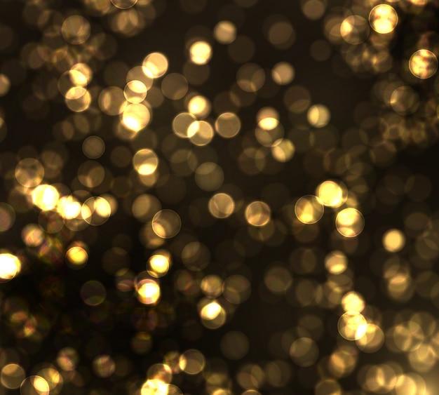 Bokeh dell'oro luce vaga su fondo nero. luci dorate glitter astratto sfocato stelle lampeggianti e scintille.