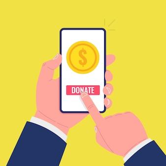 Moneta d'oro e pulsante di donazione sullo schermo dello smartphone. la mano tiene lo smartphone, il dito tocca lo schermo.