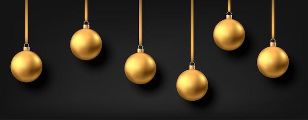 Palle di natale dorate appese isolate su sfondo nero decorazioni realistiche di palline di natale