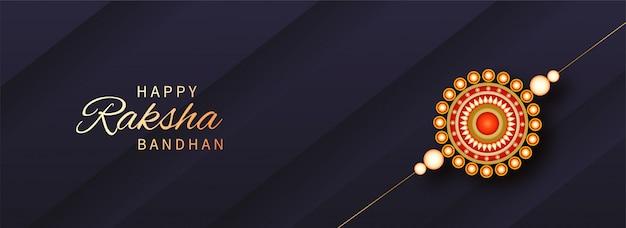 Golden raksha bandhan font con pearl rakhi (polsino) su fondo di carta diagonale viola grigiastro scuro.