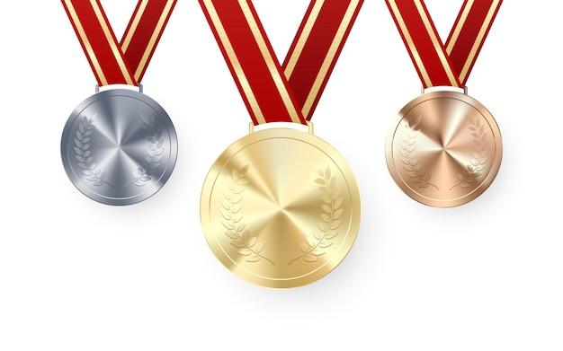 Medaglie d'oro d'argento e di bronzo con alloro appeso al nastro rosso