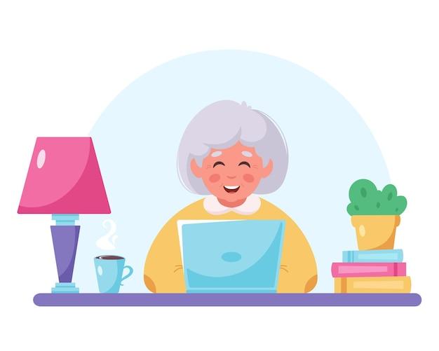 Nonna seduta con il portatile vecchia donna che usa il computer