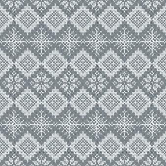Modello senza cuciture lavorato a maglia grigio con fiocchi di neve e ornamento scandinavo tradizionale.