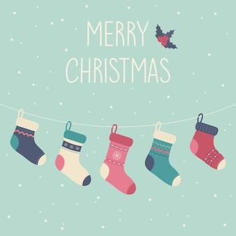 Un biglietto di auguri buon natale felice anno nuovo appendere simpatici calzini lavorati a maglia