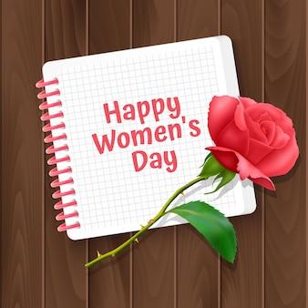 Biglietto di auguri della festa della donna, un biglietto con un taccuino e una rosa realistica
