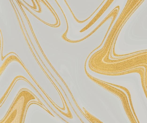 Inchiostro liquido grigio con texture glitter oro.