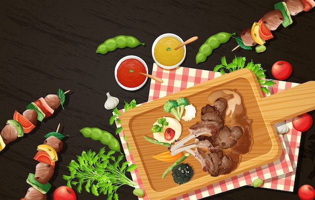 Costolette di agnello alla griglia e barbecue su tavola di legno