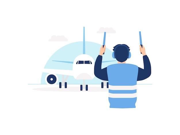 Marshaller dell'aviazione dell'equipaggio di terra che indossa un giubbotto di segnalazione che segnala l'aereo al concetto di parcheggio dell'aeroporto
