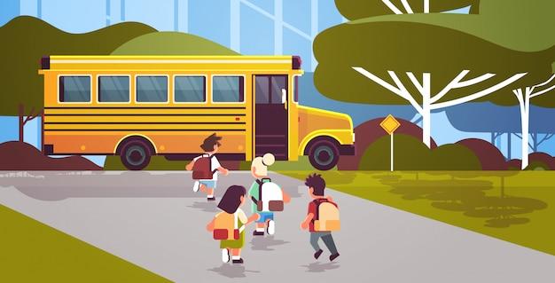 Gruppo di alunni di razza mista con zaini a piedi per autobus giallo torna a scuola allievo concetto di trasporto paesaggio sfondo piatto a figura intera orizzontale vista posteriore