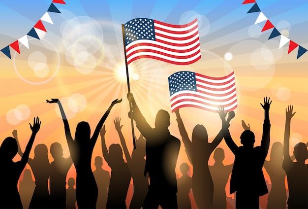 Bandiera stati uniti america della tenuta della folla della siluetta del gruppo