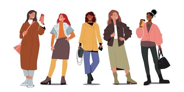 Gruppo di donne alla moda in abiti di moda autunnali. i giovani personaggi femminili indossano abiti casual moderni per la stagione autunnale