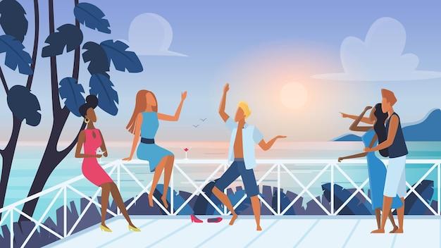 Gruppo di giovani amici che si rilassano e trascorrono del tempo insieme sulla terrazza all'aperto con vista sul mare al tramonto