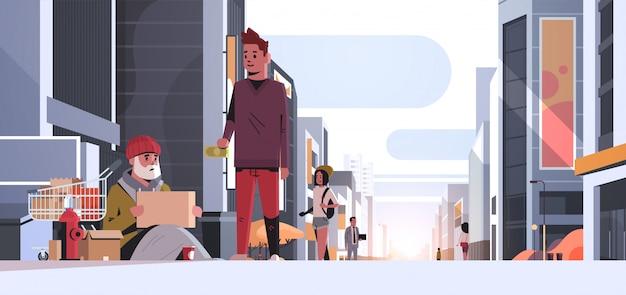 Ragazzo dando soldi povero uomo seduto piano con effetti personali nel carrello carrello chiedendo aiuto mendicante con cartello cartello senzatetto città moderna strada tramonto paesaggio urbano Vettore Premium