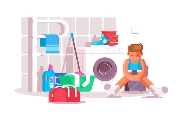 Ragazzo in lavanderia. ragazzo seduto su una sedia, utilizzando lo smartphone moderno e in attesa