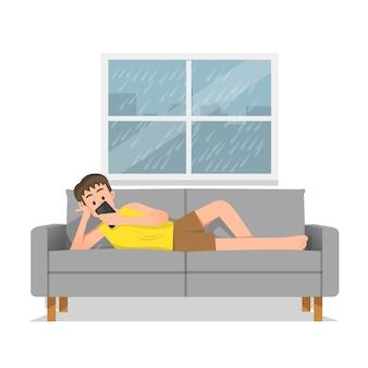 Ragazzo sdraiato sul divano in possesso di uno smartphone