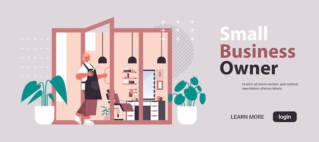 Parrucchiere in uniforme apertura porta nel salone di bellezza piccolo imprenditore concetto orizzontale a figura intera copia spazio illustrazione vettoriale