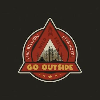 Logo di avventura disegnato a mano con tenda da campo, montagne, foresta di pini.